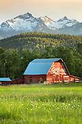Red barn beneathe the Como Peaks in the Bitterroot Valley, Montana.