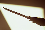 Shadow of hand holding long-bladed knife  framed in warm light of shadow from window or door