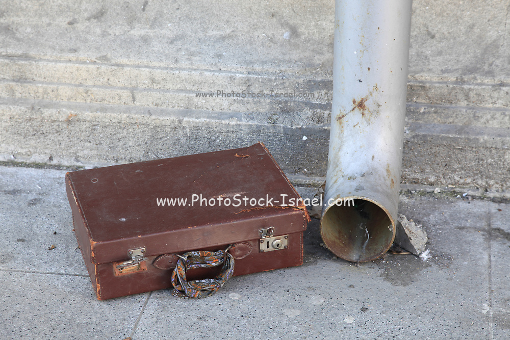 discarded old cardboard suitcase near a gutter in a street
