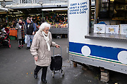 Elderly woman out shopping in Bullring Open Market, an outdoor food, fruit and vegetable market in central Birmingham on 14th March 2020 in Birmingham, United Kingdom. The Open Market offers a huge variety of fresh fruit and vegetables, fabrics, household items and seasonal goods. The Bull Ring Open Market has 130 stalls.