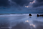 Showery weather forms dramatic skies and reflections at sunset on the wet sand of Porth Tyn Tywyn at Rhosneigr, West Anglesey.
