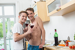 Portrait of homosexual couple having glass of wine in kitchen, smiling