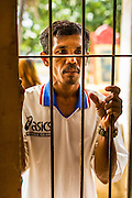 28 JUNE 2013 - PHNOM PENH, CAMBODIA:   A Cambodian man looks into a cell at the Toul Sleng Genocide Museum. The Tuol Sleng Genocide Museum is in Phnom Penh. It is a former high school that was used as the Security Prison 21 (S-21) by the Khmer Rouge from 1975 to 1979. It was used to torture and execute Cambodians and foreigners the Khmer Rouge thought were opposed to the regime.    PHOTO BY JACK KURTZ