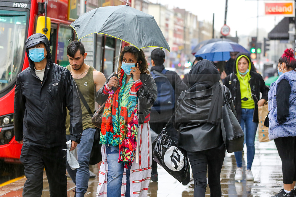 © Licensed to London News Pictures. 09/10/2020. London, UK. Members of the public wearing face coverings are caught out during heavy rainfall north London. According to the Met Office more rain is forecast for the weekend. Photo credit: Dinendra Haria/LNP