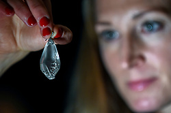 "© Licensed to London News Pictures. 22/11/2019. LONDON, UK. A staff member presents ""A Fabergé jewelled rock crystal 'snowflake' pendant"", circa 1913, by workmaster Albert Holmstrom, after the design by Alma Pihl (Est. GBP40-60k) at the preview for the upcoming sales of Russian artworks at Sotheby's New Bond Street.  The Russian Pictures and Works of Art, Fabergé and Icons sales take place on 26 November.  Photo credit: Stephen Chung/LNP"