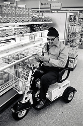 Elderly man in mobility scooter shopping in supermarket, UK 1989