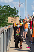 """Issac holds a sign reading """"stop the hate"""" while kneeling during the Milton Pride Rally. The I Am Alliance organized the event after an area grocery store posted an anti-mask sign which blamed the LGBTQ community for spreading COVID-19."""