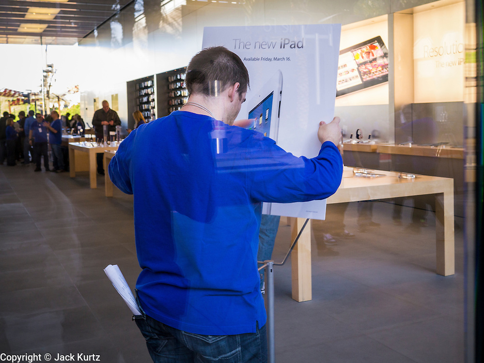 16 MARCH 2012 - SCOTTSDALE, AZ:  An Apple Store employee sets out a placard for the New iPad in the Apple Store in Scottsdale Friday. Several hundred people were in line at the Apple Store in the Scottsdale Quarter in Scottsdale, AZ, Friday to buy the New iPad.   PHOTO BY JACK KURTZ