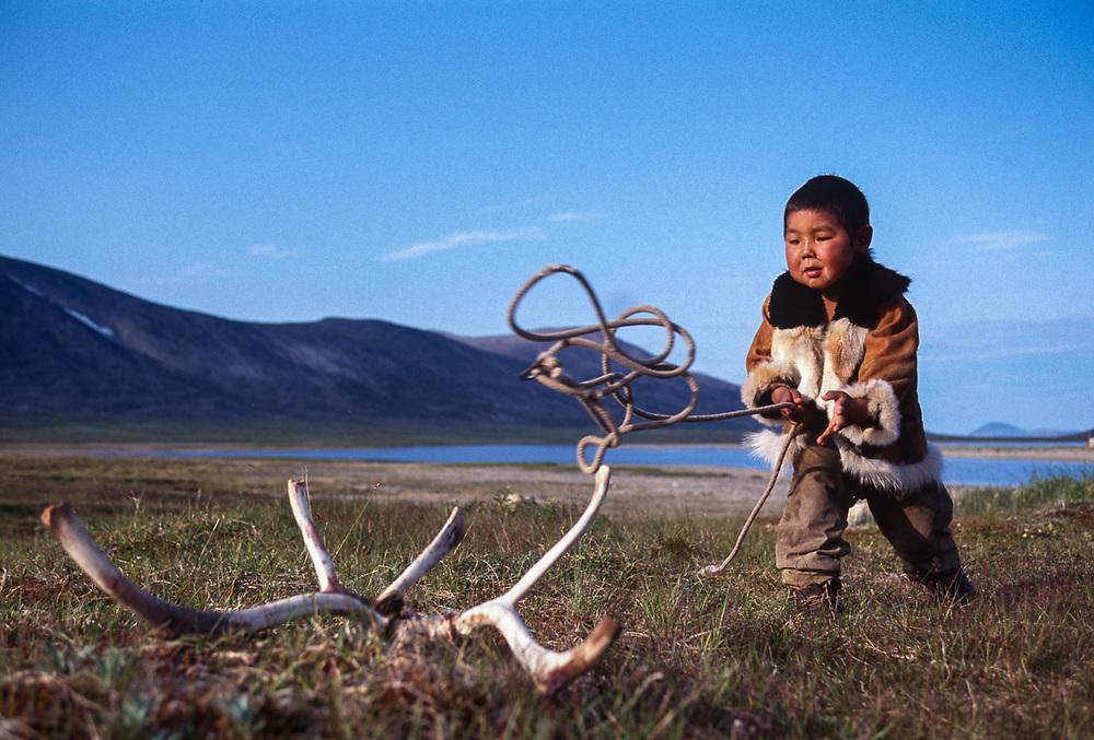 Young Chukchi boy practicing lassoeing reindeer antlers, Chukchi reindeer camp, Senyavina Strait, Chukotsk Peninsula, NE Russia, 1992