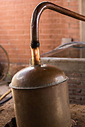 A copper still converts agave mash into alcohol at an artisanal Mezcal distillery November 5, 2014 in Matatlan, Mexico. Making Mezcal involves roasting the blue agave, crushing it and the fermenting the liquid.