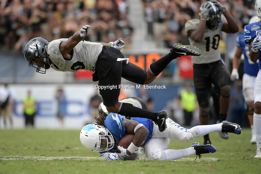 Central Florida defensive back Mike Hughes (19) flies through the air after tackling Memphis running back Darrell Henderson (8) after Henderson gained a first down during the second half of the American Athletic Conference championship NCAA college football game Saturday, Dec. 2, 2017, in Orlando, Fla. Central Florida won 62-55. (Photo by Phelan M. Ebenhack)