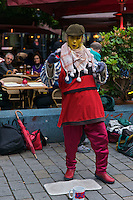 A brightly coloured costumed street performer in a busy restaurant area in Berlin.