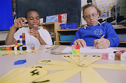 Primary school boy and girl using unilink blocks and number fans in practical maths lesson,