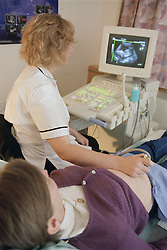 Advanced practitioner in medical ultrasound carrying out twenty week scan on maternity unit,