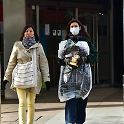A couple of women wearing a mask cross the street during Coronavirus - Pandemic hit Oxford Street many shops closure a few open but empty on 21 March 2020, UK.