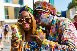 A paint and powder-covered couple pose for a picture on Ladbroke Grove as day one, Children's Day, of the Notting Hill Carnival gets underway in London. London, August 25 2019.