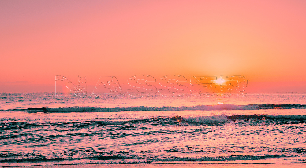 Early morning sunrise over Delray Public Beach Florida with a burst of golden sunshine reflecting over ocean waves. Highway A1A N Ocean Blvd. Biodiverse ecological beaches and oceans.