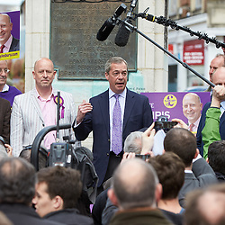 © Licensed to London News Pictures.  30/04/2015. AYLESBURY, UK. Nigel Farage (centre), UKIP party leader, gives a short speech in front of a statute of John Hampden, an parliamentarian who challenged the authority of the King ahead of the English Civil War, during a campaign visit to Aylesbury. <br /> <br /> Also in this picture: Chris Adams (left in light jacket), UKIP candidate for Aylesbury.<br /> <br /> Photo credit: Cliff Hide/LNP