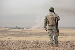 © Licensed to London News Pictures. 30/09/2015. Kirkuk, Iraq. A Kurdish peshmerga fighter views the smoke from an IED explosion which claimed the lives of five peshmerga on the outskirts of Mansoria village during an offensive aimed at capturing 11 villages from the Islamic State near Kirkuk, Iraq.<br /> <br /> Supported by large amounts of coalition airstrikes, members of the Iraqi-Kurdish peshmerga today (30/09/2015) took part in an offensive to take seven villages across a large front near Kirkuk, Iraq. By mid afternoon the Kurds had reached most of their objectives, but suffered around 10 casualties all to improvised explosive devices. All seven villages were originally Kurdish and settled with other ethnic groups during the Iraqi Arabisation process of the 1970's and 80's. Photo credit: Matt Cetti-Roberts/LNP