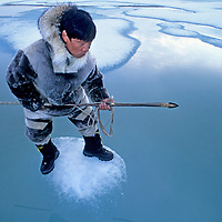 Inuit hunter Jayko Apak waits for seals on ice floe, Baffin Island, Nunavut.