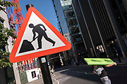 In the week that many more Londoners returned to their office workplaces after the Covid pandemic, a construction worker carries materials next to a Man at Work sign in the City of London, the capitals financial district, on 8th September 2021, in London, England.