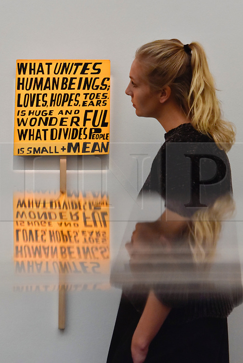 """© Licensed to London News Pictures. 12/10/2017. London, UK.  A staff member views """"What Unites Human Beings"""", 2017, by Bob and Roberta Smith (Est. GBP2.5-3.5k) at a preview of artworks for the """"Art for Grenfell"""" auction taking place at Sotheby's, New Bond Street, on 16 October.  Leading contemporary artists have agreed to donate works to the auction, the proceeds of which will be divided equally amongst the 158 surviving families of the Grenfell Tower fire by the Rugby Portobello Trust charity. Photo credit : Stephen Chung/LNP"""