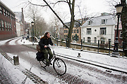 Een fietser rijdt door de een dun laagje sneeuw. Utrecht is bedekt met een heel dun laagje sneeuw.<br /> <br /> A cyclist is riding in the first snow in Utrecht.