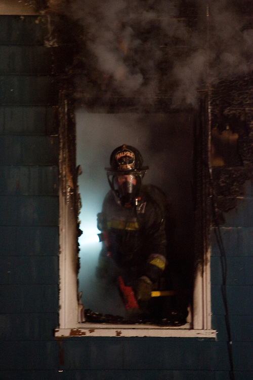 Westwood, MA 03/31/2011.A Walpole firefighter peers out a burned out .2nd floor window during a 3 alarm fire at Washington St. and Dean in Westwood early Thursday morning..Alex Jones / www.alexjonesphoto.com