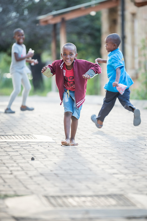 """2 March 2017, Morija, Maseru district, Lesotho: Children of resident staff at Scott Hospital playing at the hospital grounds. Scott Hospital is run by the Lesotho Evangelical Church in Southern Africa and is a founding member of the Christian Health Association of Lesotho. It is located in the village of Morija, and operates and supervises clinics in the Maseru District of Lesotho. Scott started out as a dispensary in 1864, and today offers comprehensive healthcare Mondays-Fridays, as well as pharmaceutical services around the clock. Lesotho suffers from high numbers in Tuberculosis in disesase and mortality, and so the hospital screens all patients for TB. The hospital observes among many patients what they describe as """"low health-seeking behaviour"""", services are increasing and demand rising, but space and human resources are a challenge, as is funding. I key concern is one of infrastructure, where the original design of the hospital matches poorly with current needs, as departments and buildings are scattered, posing a challenge for security. Another challenge is to adapt donation structures, so as to be able to receive payments electronically. The hospital has one ambulance, which they describe as not enough, but what they have. Another challenge is that lack of funds affects maintenance of buildings and infrastructure, as the immediate care of patients take priority. PLEASE NOTE: This photo is not to be used in social media."""