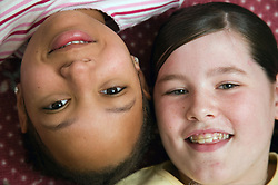 Two friends; lying on the floor smiling,