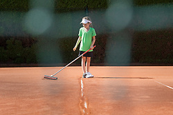Young girl preparing tennis court with broom, Bavaria, Germany