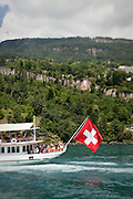 A Swiss flag drapes off the back of a paddlewheel steamboat cruising the waters of Lake Lucerne, Switzerland.