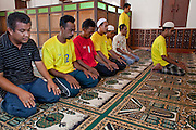 "Sept. 24, 2009 -- PATTANI, THAILAND: Muslim men pray at Krue Se Mosque in Pattani, Thailand. The Krue Se Mosque is one of Thailand's most historic mosques and long a flash point in Muslim - Buddhist confrontation. The mosque was first destroyed by advancing Thais when Pattani was an independent kingdom in 1786. It was restored in the 1980's but heavily damaged by rockets fired by unknown assailants in 2005. It has since been partially restored by local Muslims and the Thai government. Thailand's three southern most provinces; Yala, Pattani and Narathiwat are often called ""restive"" and a decades long Muslim insurgency has gained traction recently and nearly 4,000 people have been killed since 2004. The three southern provinces are under emergency control and there are more than 60,000 Thai military, police and paramilitary militia forces trying to keep the peace battling insurgents who favor car bombs and assassination.    Photo by Jack Kurtz / ZUMA Press"