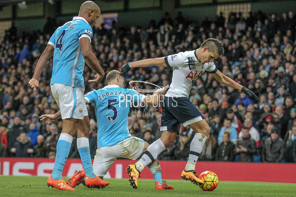 Érik Lamela (Tottenham Hotspur) runs the ball into the corner in injury time to count down the clock. Vincent Kompany (Captain) (Manchester City) and Pablo Zabaleta (Manchester City) come across to tackle him during the Barclays Premier League match between Manchester City and Tottenham Hotspur at the Etihad Stadium, Manchester, England on 14 February 2016. Photo by Mark P Doherty.