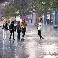 Torrential rain during the opening day of Liverpool One.  Despite the rain some people remain happy.