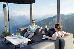 Young couple drinking wines on terrace, Zillertal, Tyrol, Austria