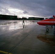 Engineering ground staff member of the Red Arrows, Britain's RAF aerobatic team, walks across a wintry airfield apron.