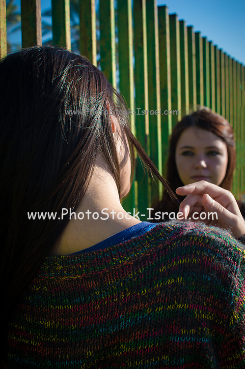 Two girlfriends interacting outdoors one facing the camera the other has her back to the camera.