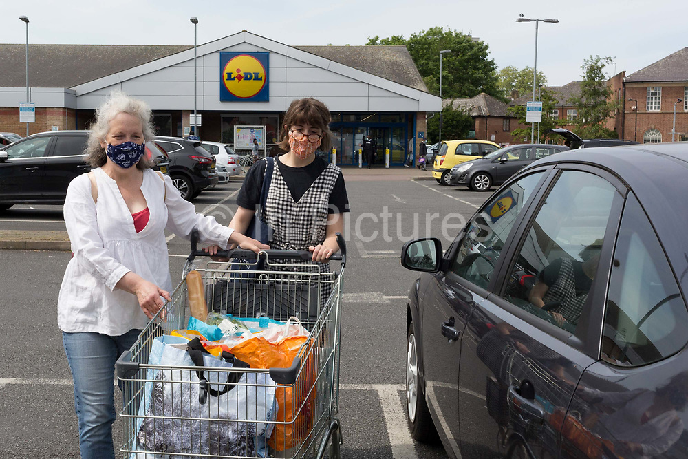 On the Friday May Bank Holiday in the UK and during the UKs Coronavirus pandemic lockdown, two women wearing home-made masks emerge from a branch of Lidl supermarket in Peckham, on 8th May 2020, in London, England.