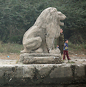 North Koreans walk past a stome lion on a pier in the town of Sunuiju October 10, 2006.  DPRK, north korea, china, dandong, border, liaoning, democratic, people's, rebiblic, of, korea, nuclear, test, rice, japan, arms, race, weapons, stalinist, communist, kin jong il