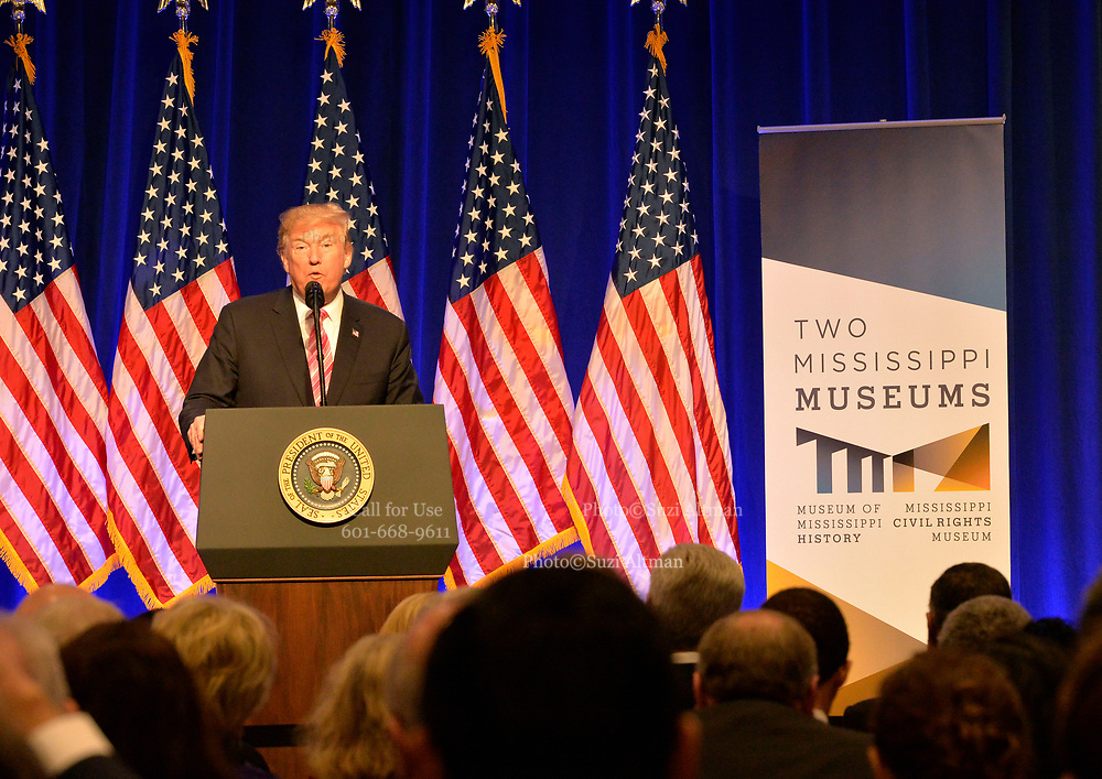 """Photo ©Suzi Altman 12/9/17 Jackson,MS    Trump spoke to a small private group of civil rights icons, museums directors, and other elected officials including MS. Governor Phil Bryant in the auditorium after his brief tour of the museum. Trump said """"the Civil Rights Museum is a tribute to our nation and to the State of Mississippi """" and he paid tribute to other leaders of the civil rights movement including James Meredith and Medgar Evers . Trumps appearance was controversial to many residents of the state of Mississippi and protests were scattered around the museums exterior.   Myrlie Evers- William widow of slain civil rights icon Medgar Evers attended the opening of the Mississippi Civiil Rights and History Museums. Evers spoke to the crowd outside after President Trump made private remarks inside to a closed audience of invited guests and press only. <br />  Right before the ribbon cutting ceremony outside on the podium Mrs Evers said """" These museums are priceless, going through the museum of my history I felt the bullets and the fears, but I also felt the hope."""" President Trump had a very short private tour of the Civil Rights Museum and did not mingle outside or stop to talk with any visitors to the new Civil Rights  museum. Photo©SuziAltman"""