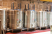 "Stainless steel fermentation tanks with on top equipment for doing ""pigeage"". Pigeage means pushing down the ""cap"" of grape skins and other solid material that floats to the surface down into the must to get better extraction. Traditionally done by foot or with a hand tool, now done with hydraulic equipment. Each of the four black columns is a mechanical ""foot"".  Domaine E Guigal, Ampuis, Cote Rotie, Rhone, France, Europe"