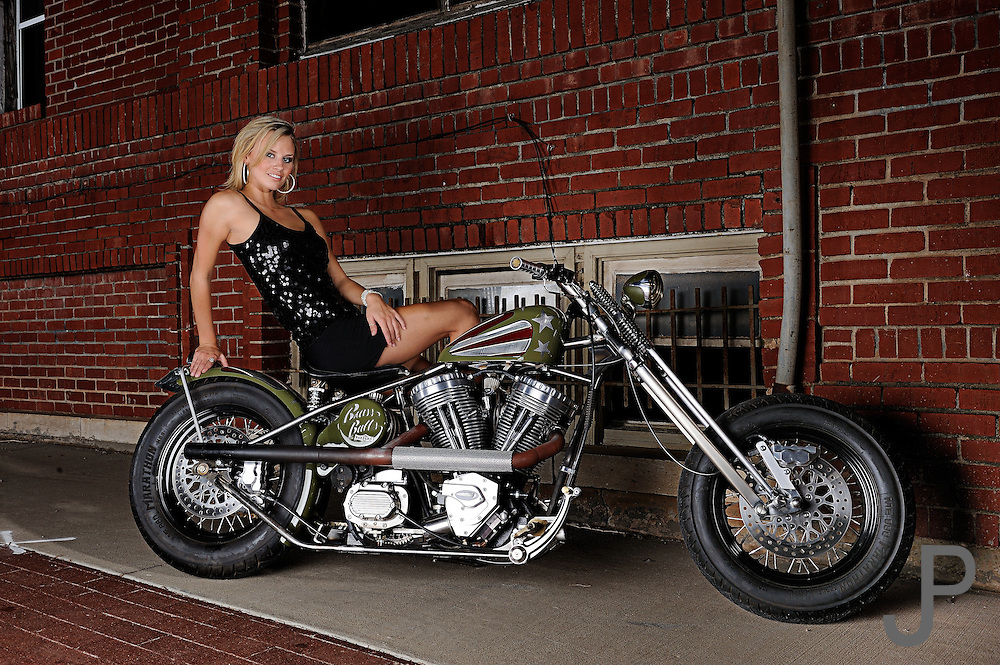 Hot sexy girl in evening dress on Brass Ball Bobber motorcycle in urban setting in front of brick wall.  Model and product released.