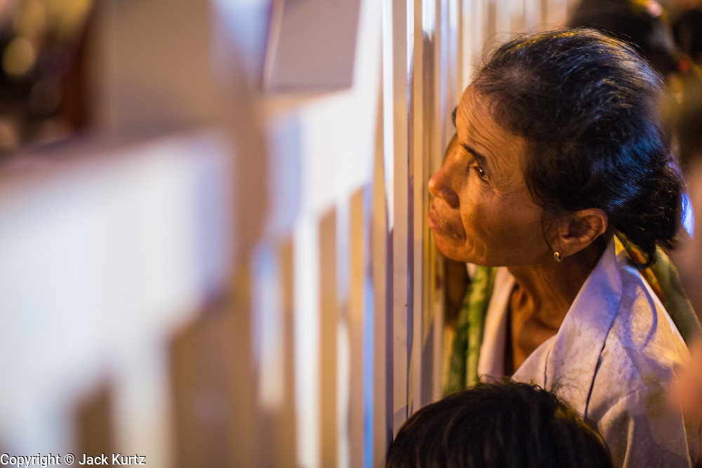 """03 FEBRUARY 2013 - PHNOM PENH, CAMBODIA:  A Cambodian woman looks through the wall surrounding the National Museum to watch the final Buddhist chanting service for former Cambodian King Norodom Sihanouk in the crematorium built for the King's funeral at the National Museum in Phnom Penh. Norodom Sihanouk (31 October 1922- 15 October 2012) was the King of Cambodia from 1941 to 1955 and again from 1993 to 2004. He was the effective ruler of Cambodia from 1953 to 1970. After his second abdication in 2004, he was given the honorific of """"The King-Father of Cambodia."""" He served as puppet head of state for the Khmer Rouge government in 1975-1976, before going into exile. Sihanouk's actual period of effective rule over Cambodia was from 9 November 1953, when Cambodia gained its independence from France, until 18 March 1970, when General Lon Nol and the National Assembly deposed him. Upon his final abdication in 2004, the Cambodian throne council appointed Norodom Sihamoni, one of Sihanouk's sons, as the new king. Sihanouk died in Beijing, China, where he was receiving medical care, on Oct. 15, 2012. His cremation will take place on Feb. 4, 2013. Over a million people are expected to attend the service.    PHOTO BY JACK KURTZ"""