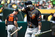 San Francisco Giants first baseman Brandon Belt (9) wipes his face after striking out against the Oakland Athletics at Oakland Coliseum in Oakland, California, on March 25, 2018. (Stan Olszewski/Special to S.F. Examiner)