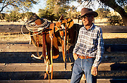 Roy Salge with saddle he hand made, corral, Vera Earl Ranch, near Sonoita, Arizona.©1991 Edward McCain. All rights reserved. McCain Photography, McCain Creative, Inc.