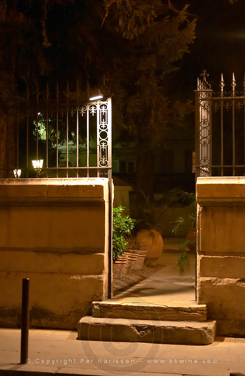 An open gate in a stone wall lit by strong overhead floodlight at night opening into a dark garden.  Avignon, Vaucluse, Provence, Alpes Cote d Azur, France, Europe