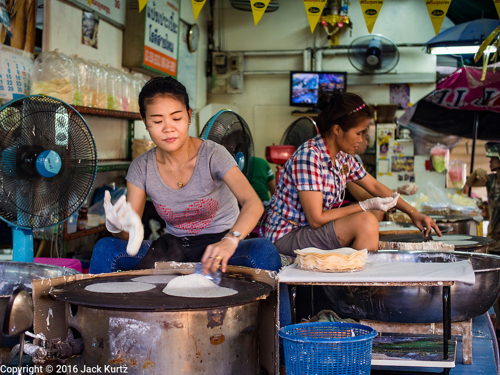 """12 JANUARY 2016 - BANGKOK, THAILAND: Women make """"roti,"""" a type of grilled flat bread, in Khlong Toey Market in Bangkok. Khlong Toey (also called Khlong Toei) Market is one of the largest """"wet markets"""" in Thailand. Roti is originally from India and came to Thailand via Indian immigrants who settled in Thailand in the 1800s. The market is located in the midst of one of Bangkok's largest slum areas and close to the city's original deep water port. Thousands of people live in the neighboring slum area. Thousands more shop in the sprawling market for fresh fruits and vegetables as well meat, fish and poultry.         PHOTO BY JACK KURTZ"""