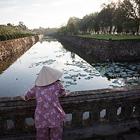 A woman overlooks the moat near the  Meridian Gate at the Imperial City, a UNESCO World Heritage Site, in Hue, Vietnam. Locals gather at the Citadel that surrounds the Imperial City in the cool early morning hours just after sunrise to walk, exercise and relax.