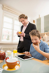 Boy using digital tablet during breakfast with father watching
